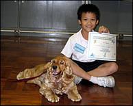 Glad pojke med hund och hundambassadörscertifikat på Professor Paws utbildningsprogram i Kina