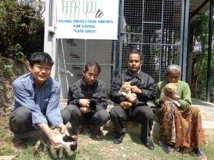Människor och katter poserar framför skylt som tackar Animal Protection Network för all hjälp